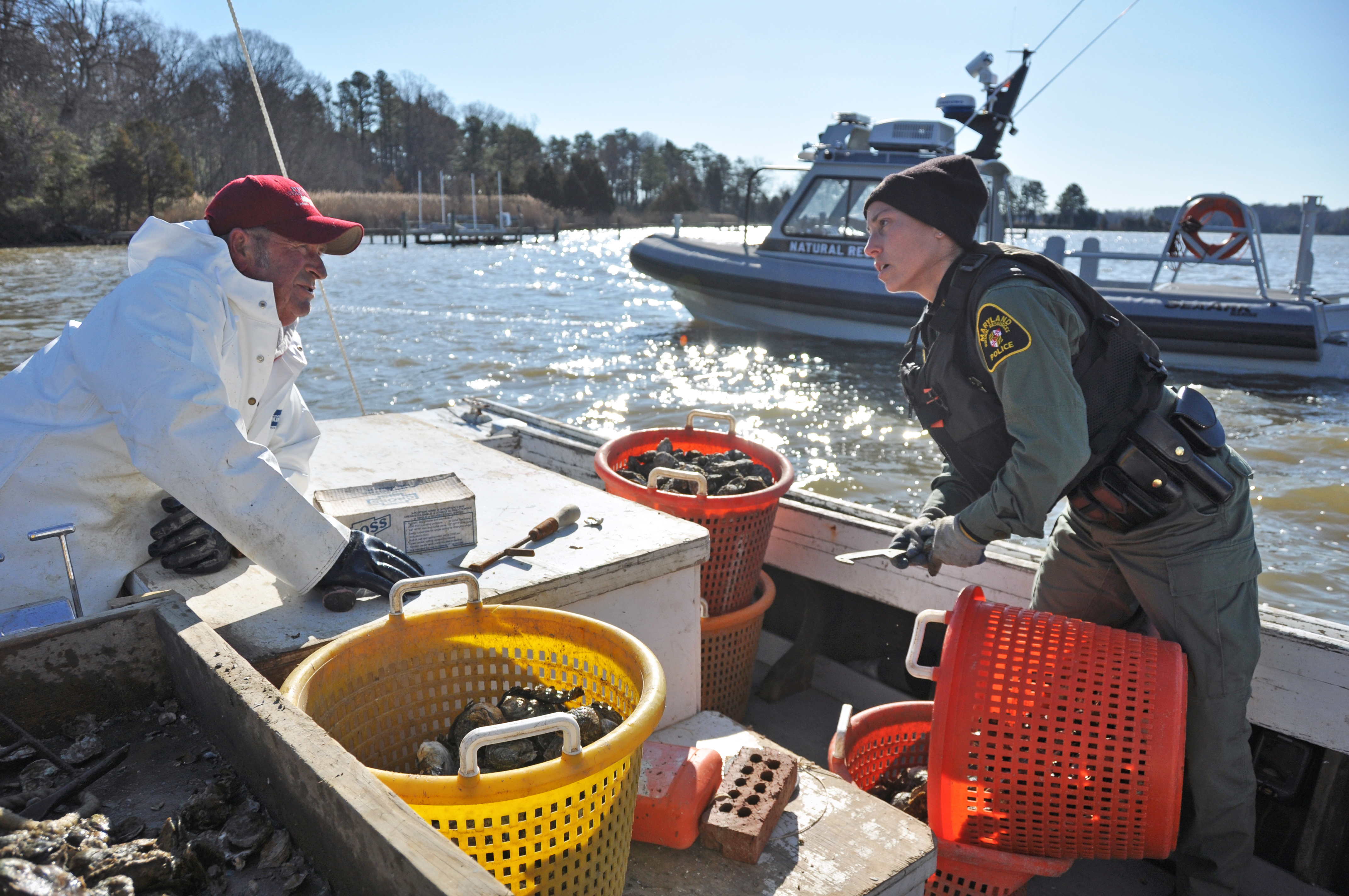 Maryland Natural Resources Police officer and a Chesapeake Bay waterman, photo by multimedia journalist and environment reporter Pamela Wood.