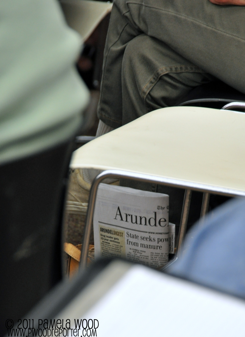 The Capital newspaper sticking out of a woman's purse, photo by multimedia journalist and environment reporter Pamela Wood.